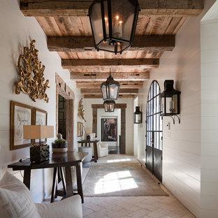На фото: класса люкс большие коридоры в средиземноморском стиле с белыми стенами, полом из известняка и бежевым полом