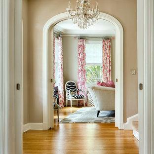 Inredning av en klassisk hall, med beige väggar, mellanmörkt trägolv och gult golv