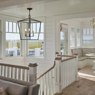 Cette photo montre un grand couloir bord de mer avec un mur blanc, un sol en bois brun et un plafond en bois.