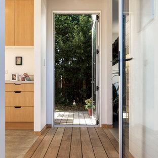 Cette image montre un couloir design avec un mur blanc, un sol en bois brun, un sol beige et un plafond en poutres apparentes.