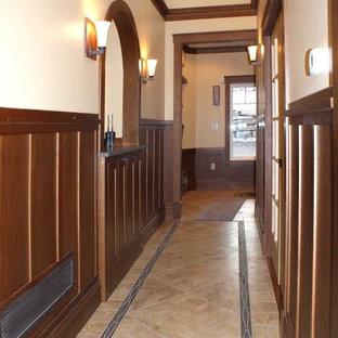 Exemple d'un couloir chic de taille moyenne avec un sol en travertin et un mur beige.