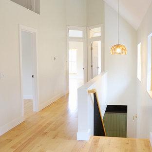 Modern inredning av en mellanstor hall, med vita väggar, mellanmörkt trägolv och brunt golv