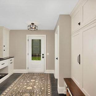 シカゴの中サイズのトランジショナルスタイルのおしゃれな廊下 (ベージュの壁、ラミネートの床、黒い床) の写真