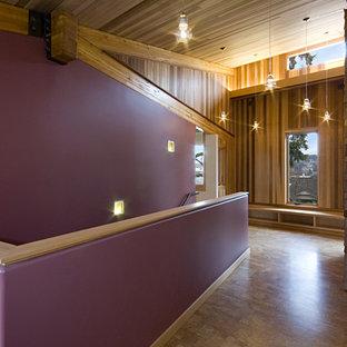 Bild på en mellanstor funkis hall, med lila väggar och mellanmörkt trägolv