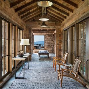 他の地域の広いラスティックスタイルのおしゃれな廊下 (茶色い壁、グレーの床) の写真