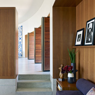 Large trendy concrete floor and gray floor hallway photo in Los Angeles with white walls