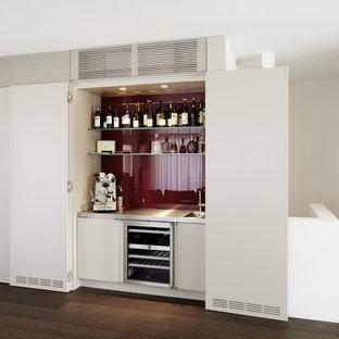 フランクフルトの中サイズのコンテンポラリースタイルのおしゃれなホームバー (一体型シンク、フラットパネル扉のキャビネット、白いキャビネット、赤いキッチンパネル、濃色無垢フローリング) の写真