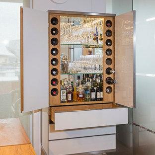 Imagen de bar en casa actual, pequeño, con armarios con paneles lisos, puertas de armario blancas, suelo de madera en tonos medios, encimera de madera y salpicadero con efecto espejo