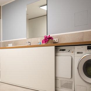 Esempio di una grande lavanderia multiuso contemporanea con lavello da incasso, ante lisce, ante bianche, pareti grigie e lavasciuga