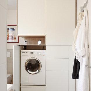 Immagine di una piccola sala lavanderia design con ante lisce, top in legno, pareti beige, pavimento con piastrelle in ceramica, lavatrice e asciugatrice nascoste, pavimento nero e ante bianche