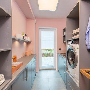 Cette image montre une buanderie parallèle design multi-usage et de taille moyenne avec un évier posé, un placard à porte plane, des portes de placard grises, un mur rose, un sol gris et un plan de travail gris.