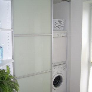 Exempel på en mellanstor modern linjär liten tvättstuga, med en nedsänkt diskho, luckor med glaspanel, vita skåp, träbänkskiva, vita väggar, klinkergolv i porslin, en tvättpelare och beiget golv
