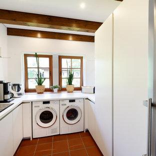 Idee per una piccola lavanderia multiuso country con lavello da incasso, ante lisce, ante bianche, pareti bianche, pavimento in terracotta, lavatrice e asciugatrice affiancate, pavimento rosso e top bianco