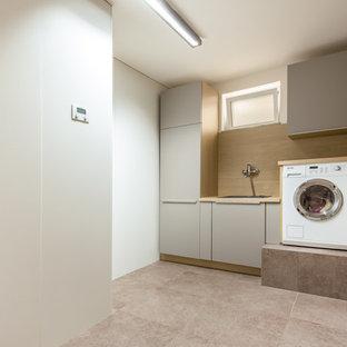 Multifunktionaler, Einzeiliger, Kleiner Moderner Hauswirtschaftsraum mit Unterbauwaschbecken, flächenbündigen Schrankfronten, beiger Wandfarbe, Kalkstein und grauen Schränken in Köln