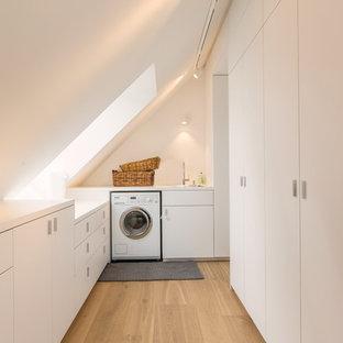Mittelgroße Moderne Waschküche in U-Form mit Einbauwaschbecken, flächenbündigen Schrankfronten, weißen Schränken, weißer Wandfarbe, hellem Holzboden und Waschmaschine und Trockner nebeneinander in München