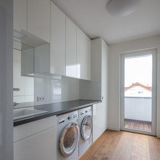 Moderner Hauswirtschaftsraum mit weißen Schränken, weißer Wandfarbe und gebeiztem Holzboden in Köln