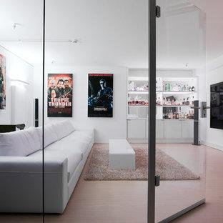 Mittelgroßes, Abgetrenntes Modernes Heimkino Mit Weißer Wandfarbe, Hellem  Holzboden Und Wand TV In