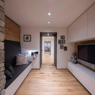 Immagine di un piccolo home theatre shabby-chic style aperto con pareti bianche, pavimento in legno massello medio, parete attrezzata e pavimento marrone