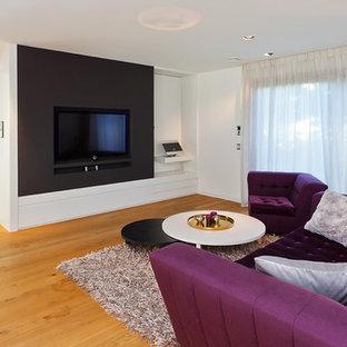 Foto di un home theatre minimal di medie dimensioni e aperto con pareti bianche, pavimento in legno verniciato e parete attrezzata