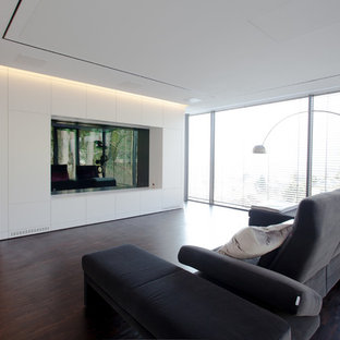 Inspiration for a large modern open concept home theatre in Frankfurt with white walls, dark hardwood floors and a built-in media wall.