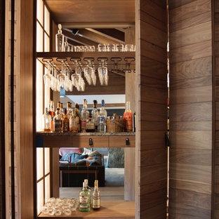 巨大なモダンスタイルのおしゃれなホームバー (シンクなし、家具調キャビネット、中間色木目調キャビネット、大理石カウンター、ミラータイルのキッチンパネル、無垢フローリング) の写真