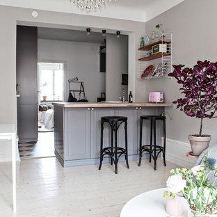 Inspiration för små minimalistiska hemmabarer med stolar, med ljust trägolv, luckor med upphöjd panel, grå skåp och träbänkskiva