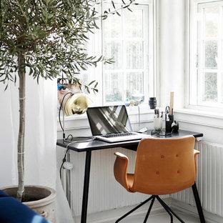 Inspiration för ett litet skandinaviskt hemmabibliotek, med vita väggar, målat trägolv och ett fristående skrivbord