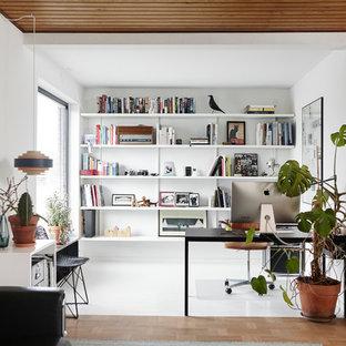 Foto på ett stort 60 tals hemmabibliotek, med vita väggar, ett fristående skrivbord och flerfärgat golv