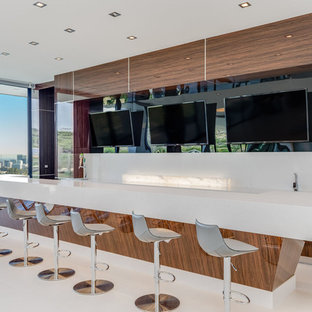 Large minimalist u-shaped porcelain tile and white floor home bar photo in Los Angeles with a drop-in sink, recessed-panel cabinets, medium tone wood cabinets, quartz countertops, white backsplash, quartz backsplash and white countertops