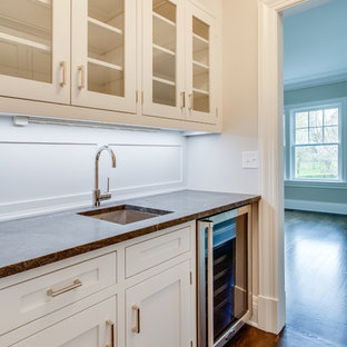 Design ideas for a large traditional u-shaped wet bar in Other with a submerged sink, glass-front cabinets, white cabinets, marble worktops, white splashback, medium hardwood flooring and brown floors.