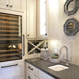 デトロイトのトラディショナルスタイルのおしゃれなウェット バー (L型、アンダーカウンターシンク、落し込みパネル扉のキャビネット、白いキャビネット、白いキッチンパネル、濃色無垢フローリング、ライムストーンのキッチンパネル) の写真