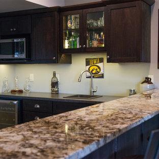 Foto di un grande bancone bar stile americano con ante in stile shaker, ante in legno bruno, lavello da incasso, top in laminato e pavimento in travertino