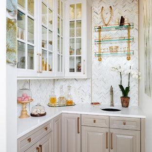 Foto di un piccolo angolo bar con lavandino tradizionale con paraspruzzi grigio, lavello sottopiano, ante con bugna sagomata, ante beige e top bianco