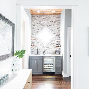 チャールストンの小さいカントリー風おしゃれなウェット バー (シェーカースタイル扉のキャビネット、グレーのキャビネット、レンガのキッチンパネル、I型、アンダーカウンターシンク、白いキッチンパネル、濃色無垢フローリング、茶色い床、白いキッチンカウンター) の写真