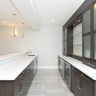 Exemple d'un bar de salon parallèle moderne de taille moyenne avec un bar à boissons, un évier encastré, un placard à porte plane, des portes de placard en bois sombre, un plan de travail en surface solide, un sol en carrelage de porcelaine, un sol gris et un plan de travail blanc.