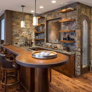 Seated home bar - mid-sized rustic u-shaped medium tone wood floor and brown floor seated home bar idea in Salt Lake City with dark wood cabinets, stone tile backsplash, brown countertops, recessed-panel cabinets, wood countertops and brown backsplash