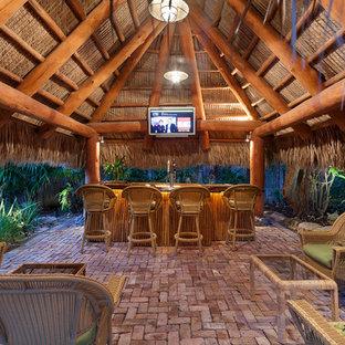 マイアミの巨大なおしゃれな着席型バー (ドロップインシンク、木材カウンター、レンガの床、ピンクの床、茶色いキッチンカウンター) の写真