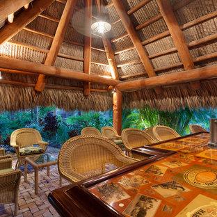 マイアミの巨大なおしゃれな着席型バー (フラットパネル扉のキャビネット、レンガの床、ピンクの床、マルチカラーのキッチンカウンター) の写真