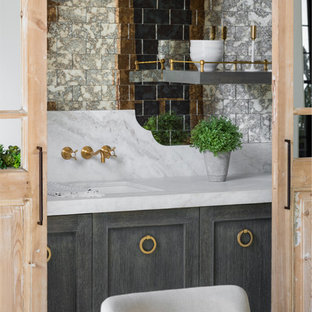 This is an example of a medium sized farmhouse single-wall wet bar in Phoenix with a submerged sink, shaker cabinets, grey cabinets, marble worktops, multi-coloured splashback, mirror splashback, light hardwood flooring and white worktops.