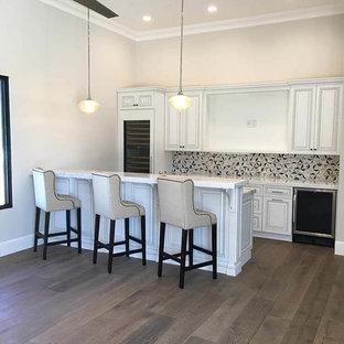 Foto di un grande angolo bar con lavandino moderno con ante con riquadro incassato, ante gialle, top in quarzite, parquet scuro, pavimento marrone e top grigio