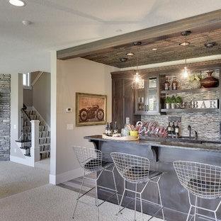 Inredning av en klassisk stor hemmabar, med luckor med glaspanel, skåp i slitet trä, stänkskydd i stickkakel, heltäckningsmatta och beiget golv