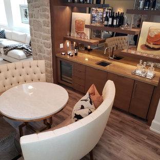 カンザスシティの中くらいの地中海スタイルのおしゃれなウェット バー (I型、アンダーカウンターシンク、フラットパネル扉のキャビネット、中間色木目調キャビネット、御影石カウンター、ミラータイルのキッチンパネル、ラミネートの床、グレーの床、茶色いキッチンカウンター) の写真