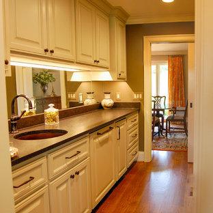 Idee per un angolo bar con lavandino boho chic di medie dimensioni con lavello sottopiano, ante con bugna sagomata, ante gialle, top in granito e pavimento in legno massello medio