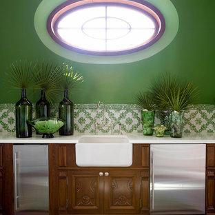 Large coastal single-wall wet bar in Jacksonville with a submerged sink, freestanding cabinets, medium wood cabinets, marble worktops, green splashback, porcelain splashback and dark hardwood flooring.
