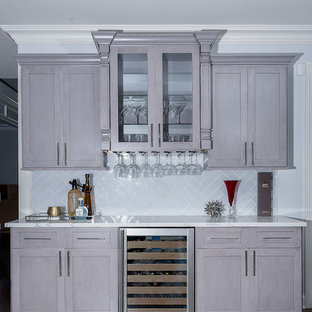 Design ideas for a medium sized traditional single-wall wet bar in New York with grey cabinets, medium hardwood flooring, shaker cabinets, marble worktops, white splashback, glass tiled splashback and brown floors.