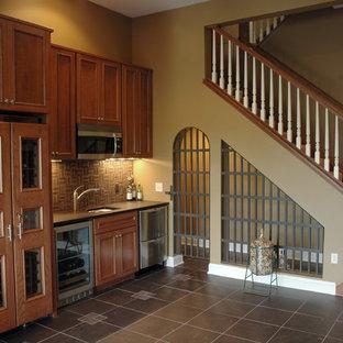 ミネアポリスの大きいトラディショナルスタイルのおしゃれなウェット バー (ll型、アンダーカウンターシンク、家具調キャビネット、濃色木目調キャビネット、ラミネートカウンター、茶色いキッチンパネル、セラミックタイルのキッチンパネル、セラミックタイルの床、茶色い床) の写真