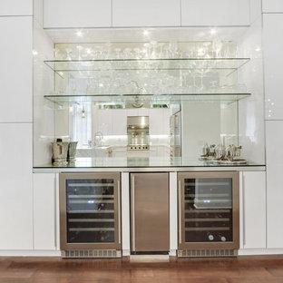 Réalisation d'un très grand bar de salon avec évier linéaire minimaliste avec un placard à porte vitrée, des portes de placard grises, un plan de travail en verre et une crédence en carreau de miroir.