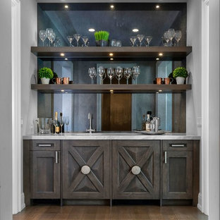 This is an example of a large classic wet bar in Detroit with distressed cabinets, marble worktops, mirror splashback, medium hardwood flooring and brown floors.