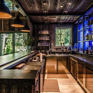 Immagine di un grande bancone bar rustico con parquet chiaro, ante in legno bruno, lavello integrato, ante lisce, top in zinco, paraspruzzi nero, paraspruzzi in lastra di pietra e pavimento beige