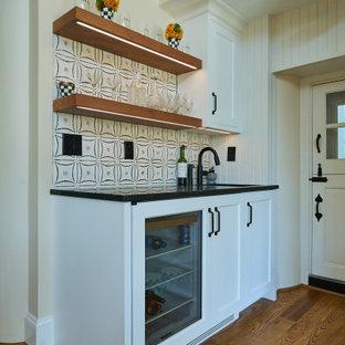 フィラデルフィアの広いカントリー風おしゃれなホームバー (アンダーカウンターシンク、シェーカースタイル扉のキャビネット、白いキャビネット、クオーツストーンカウンター、白いキッチンパネル、磁器タイルのキッチンパネル、無垢フローリング、茶色い床、白いキッチンカウンター) の写真